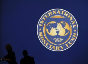Visitors are silhouetted against the logo of the International Monetary Fund at the main venue for the IMF and World Bank annual meeting in Tokyo October 10, 2012. Japan is scheduled to host the IMF and World Bank annual meetings for the first time in nearly half a century. About 20,000 people are expected to attend the event, making it one of the world's largest international conferences. REUTERS/Kim Kyung-Hoon (JAPAN - Tags: BUSINESS POLITICS LOGO)